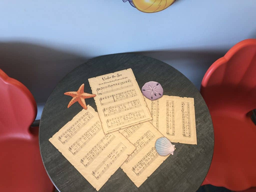 A table with musical scores on it inside the Art of Animation Little Mermaid standard room