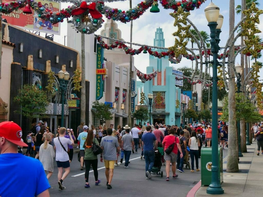 Main street in Hollywood Studios with Christmas decorations and people walking along