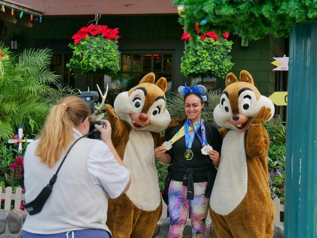 Chip and Dale taking a photo with a guest with Christmas decorations behind them at Hollywood Studios at Christmas