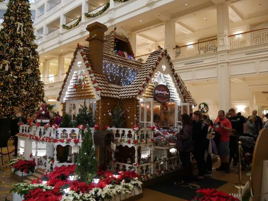 A gingerbread house with people shopping at the Grand Floridian Disney World resort at Christmas