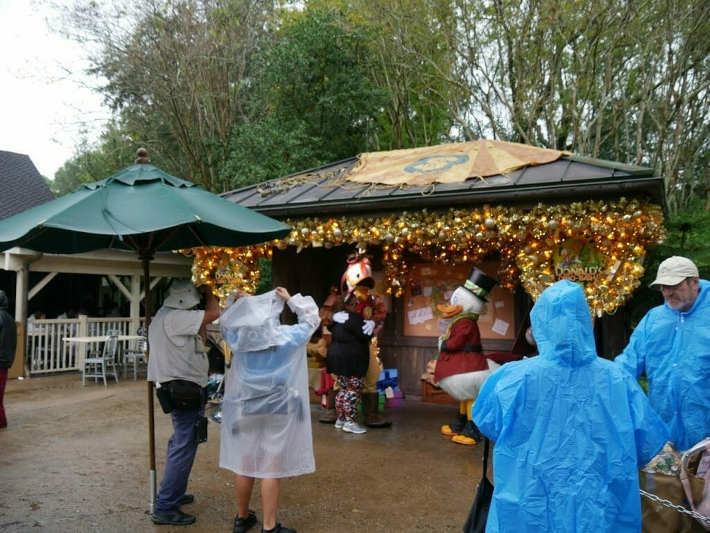 Characters under a hut decorated for Christmas, greeting guests