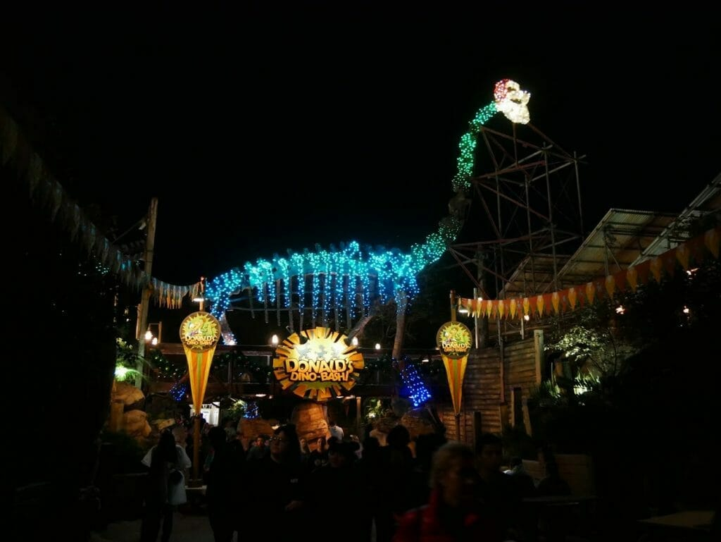 Large dinosaur with Santa hat and beard on lit up at night at Disney World's Animal Kingdom at Christmas