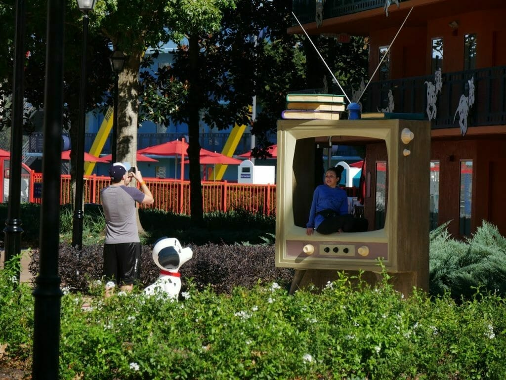 Some people taking a picture sitting inside a large TV with a Dalmatian looking on at Disney All Star Movies resort