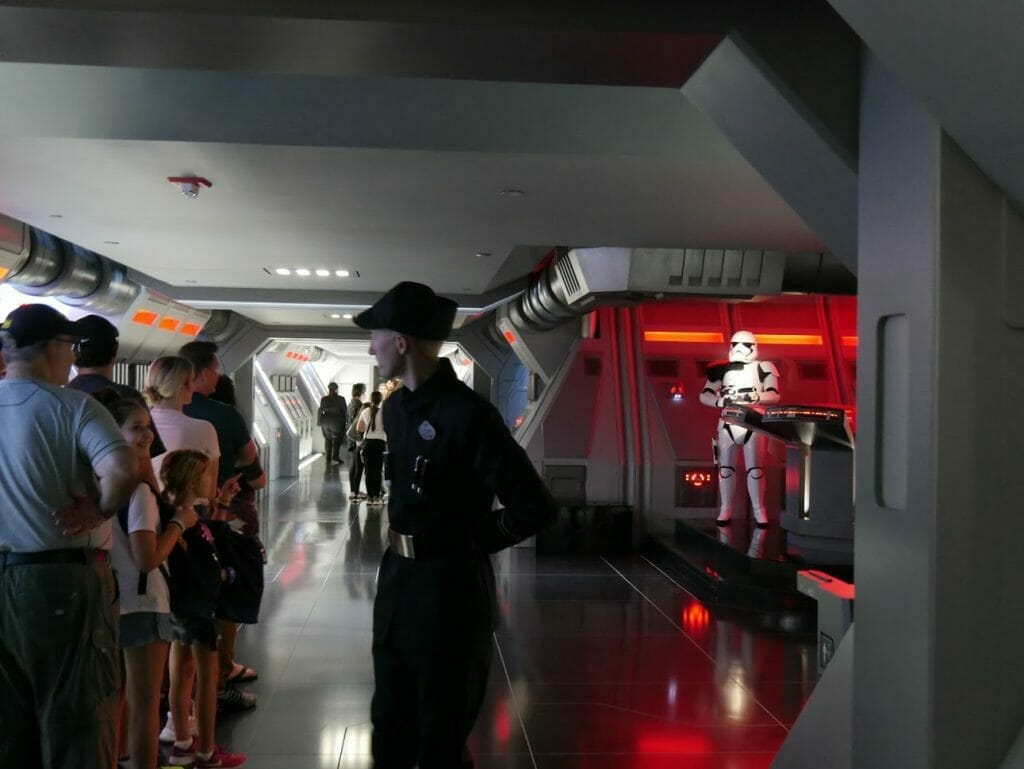 An Imperial soldier with Stormtroopers behind and people queueing