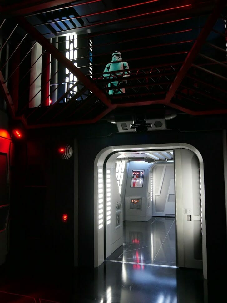 A Stormtrooper looking down on a group in a holding cell in Rise of the Resistance at Hollywood Studios