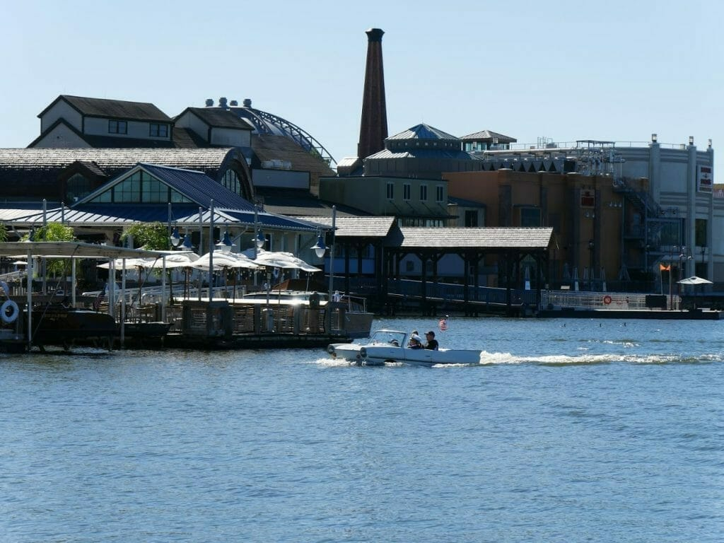 A group of people sailing a car boat on the water at Disney Springs in Disney World