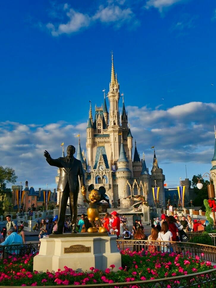 A Walt and Mickey Mouse statue in front of the Disney World Magic Kingdom castle