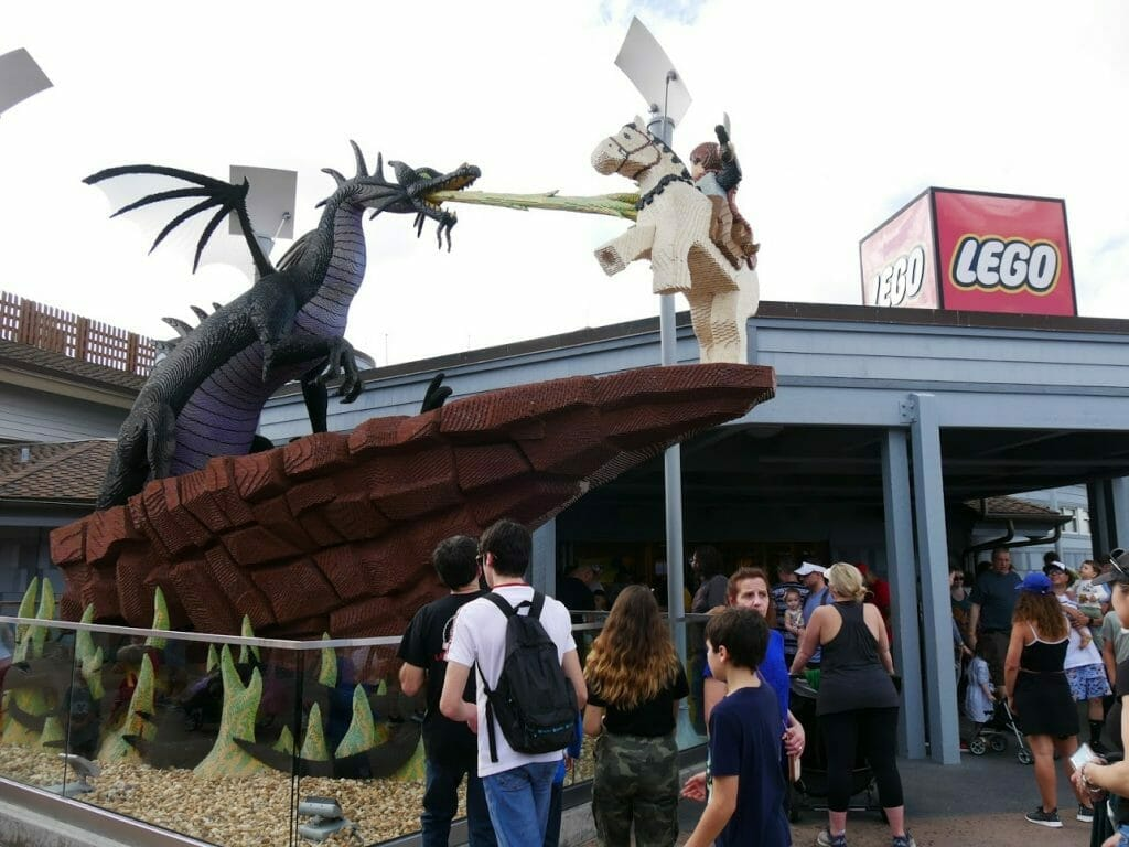 Entrance to the Lego store at Disney Springs with a lego dragon breathing fire and a Lego knight fighting it