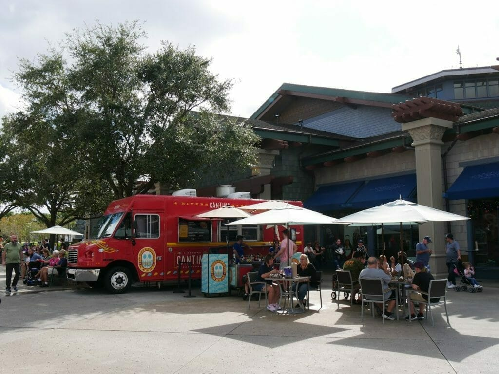 A red food truck with tables outside at Disney Springs