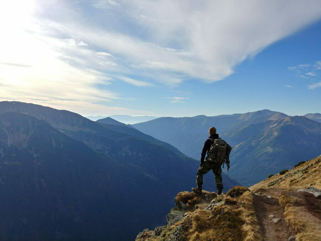 person standing on edge of cliff looking at mountains