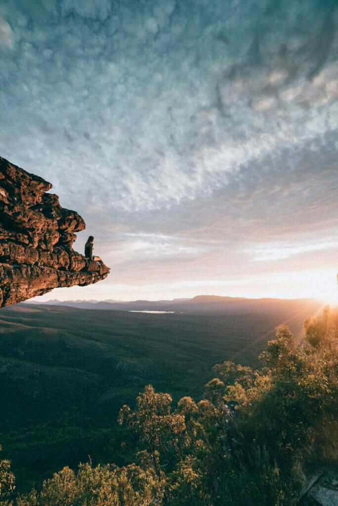 man sitting on edge of rock