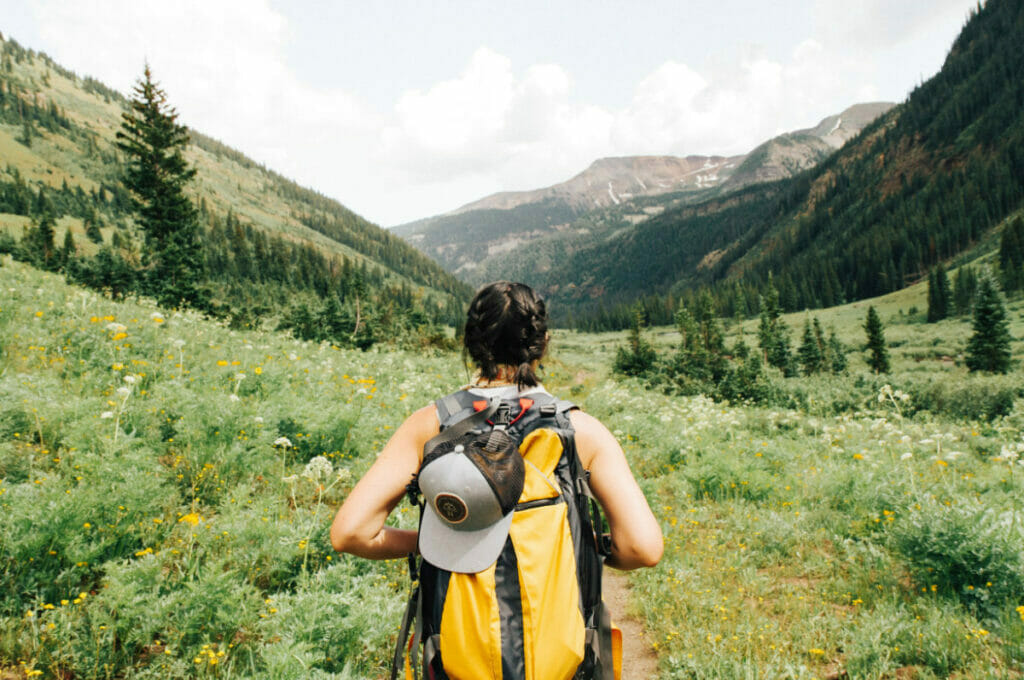 girl with backpack looking out into the mountains