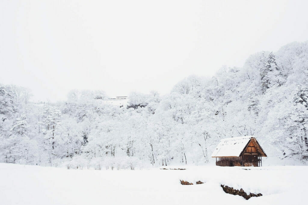 snow covered landscape with small cabin