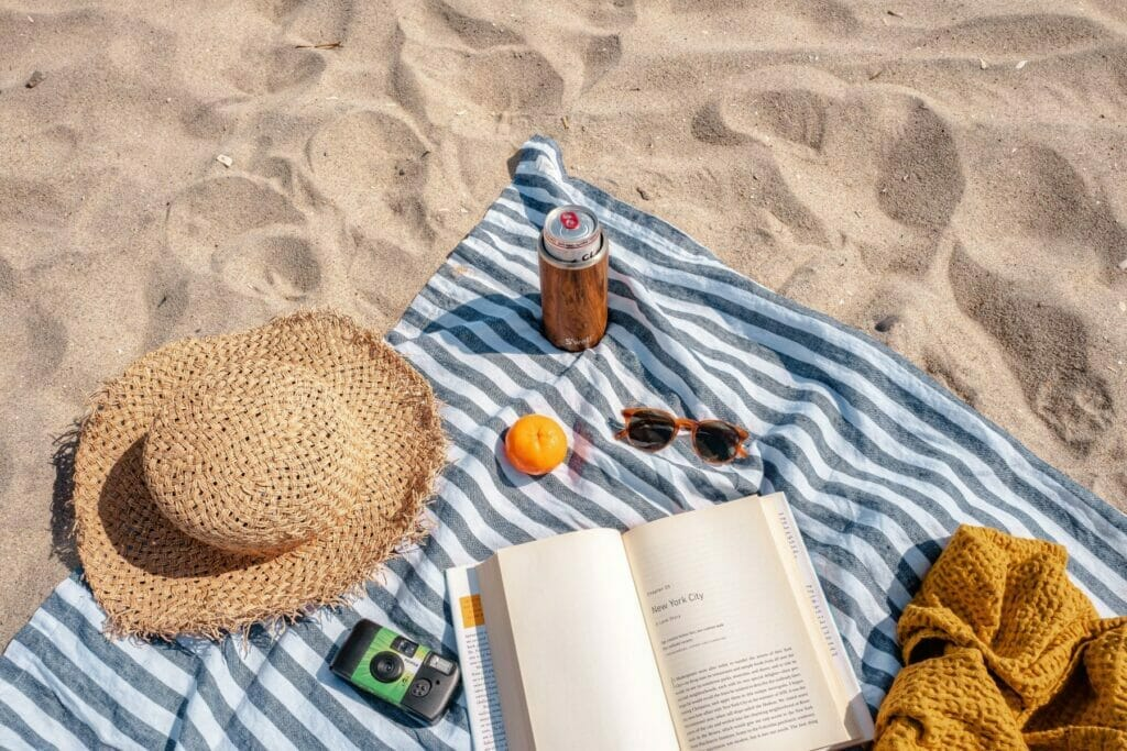 hat blanket and book on the sand