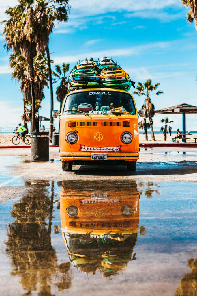 van with surfboards on a beach